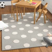 Set a soothing foundation for your little one's space with this handmade gray and ivory area rug, showcasing a polka dot motif in calming hues. Made in India, this area rug is hand-tufted from 100% wool in a medium 0.63