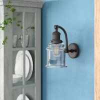 When it comes to good lighting, your light fixture can make it or break it. Find the light you love with this wall sconce. Affixed to your wall on a circular plate, this piece features one curved arm, evoking all the character of a country cottage in your abode. Glass shade diffuses light from an included 100 W medium-base bulb, perfect for brightening up your space in style. In order to maintain the finish on this fixture, it's recommended to use water and cheesecloth for cleaning.