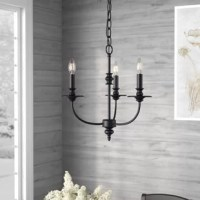 Greet guests with a warm and welcoming glow in the entryway or dress up your dining room for an upcoming dinner party with this eye-catching chandelier. Crafted from metal, it offers a more modern take on traditional with curved arms and turned silhouettes all finished in oil rubbed black for versatility. Measuring 17'' H x 18'' W x 18'' D, it includes three candelabra-inspired lights exposed to create an even gleam.