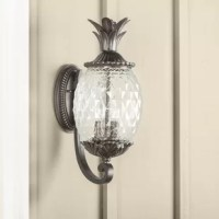 In coastal communities and seaside towns the world over, a pineapple is a sign of hospitality. In the spirit of welcome, invite guests to your warm home with this charming two-light outdoor pineapple sconce! Crafted from cast aluminum, this stylish sconce features a raised circle backplate with tasteful dentil moldings, a tall curved arm, and a pendant holder modeled after the crown of pineapple, while a clear, textured, pineapple-shaped glass shade ensconces the simple two-light fixture.