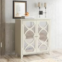 Looking for an eye-catching storage solution in the entryway, living room, or master suite? With its mirrored panels and charmingly spare silhouette, this accent cabinet ticks the boxes for both form and function. Crafted from wood, its stands atop four tapered feet and features a clean-lined body that brings the best of modern design to your abode, while curved details on the doors overlay mirrored panels for that extra pop of glam style. Inside, two shelves offer space to stash linens, books...