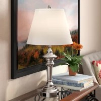 Light your home in a traditional style with this elegant and sophisticated table lamp. The white linen empire shade gives this lamp its classic style, while the brushed silver finish and deep turned base design elevate the look with artful appeal. This lovely luminary also features a USB port for added convenience. Try setting this lamp on a mahogany nightstand beside your master bed to cast a warm glow over late-night readings and breakfasts in bed, and use the USB to charge your phone...