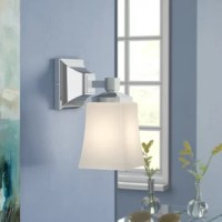 Tired of fumbling around a dimly-lit bathroom? Adding a bath sconce like this one is a great option for putting an end to makeup mishaps or lopsided hairdos by brightening up your master bath or powder room. Perfect for flanking a mirror or perched on a narrow wall, this piece features a squared bell shade crafted from frosted glass for an understated classic style. This luminary accommodates a single 60 W bulb, although none is included. And since it's designed with damp spaces in mind, it's...
