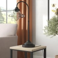 Portable and stylish, lightweight with abundant illumination – what's not to love about table lamps? Perfect in any room that needs a bit more brightness that doubles as decor, lamps like this are great additions anywhere. A great touch for an industrial look, this piece features an warm bronze finish and an iridescent amber glass shade with a top-inspired silhouette. Crafted from steel, the slender hook shape and wide shade are sure to catch the eye. Accommodates a 60 W bulb, and we include...