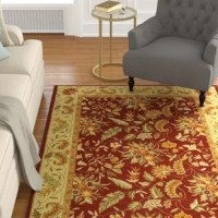 Set a garden-inspired centerpiece in your living room or entryway with this eye-catching area rug. Hand-hooked using 100% pure wool, it offers a low 0.25'' pile height for a design that's easy to clean and vacuum. Its warm hues of red and beige are perfect for more traditional spaces, while a Persian-inspired floral motif is sure to add artful intrigue. We recommend using a rug pad to keep this piece safely in place.
