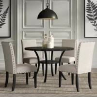 Whether hosting a dinner party with close friends or simply enjoying an everyday meal with the family, this five-piece dining set is a must-have for your home. Crafted from a blend of both solid and manufactured wood, the table strikes a circular silhouette and showcases nailhead accents around the periphery. Four upholstered chairs boast a square seat and solid back awash in a solid color, while matching nailhead accents round out the ensemble.