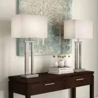 When it comes to adding both style and illumination to a room, few fixtures can beat table lamps: they're versatile, space-conscious lighting fixtures – and we can't get enough of them! Take this set of two, for example: with a clean-lined metal base and white box shade, it's sure to brighten up any contemporary space while creating a cohesive look. The base is crafted from silver-finished metal, making this neutral piece easy to fit into almost any color scheme. Each lamp accommodates one...