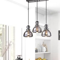 When it comes to overhead lighting, pendant lights are a fan favorite – and for good reason. They don't take up prime real estate, they offer options for up and downlighting, they work well solo and in clusters, and they come in an endless amount of styles! Take this pendant, for instance: Taking cues from classic and contemporary design aesthetics, it showcases a cluster of three bell-shaped glass shades awash in a smoke finish with bubbled accents inside. Each accommodates one 100 W E26...