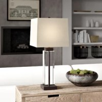 Let's be clear: this lamp looks lovely atop any console table or nightstand and is sure to stand out in your favorite spaces. A transparent glass body highlights its approachable contemporary design, while bronze-finished details add a touch of warmth to its appearance. The perfect capstone for an already distinctive look, a neutral geometric shade ties together both styles on top. This lamp measures 29.3