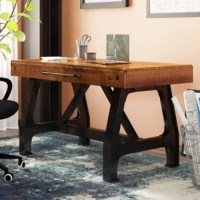Inspired by warehouse workbenches, this writing desk anchors your home office in a charming industrial style. Striking an architectural silhouette with riveted details and cross beam supports, this desk's graphite metal frame echoes cast iron machine bases from the turn of the century. Crafted of solid wood, the chunky rectangular desktop sports a distressed amber wood finish for a reclaimed vibe, with the warmth of the amber tones in the acacia wood, combined with the graphite finishes on...