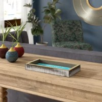 Multi-functional accent trays can be used in any room. Put them on an entryway table to hold other decorative items or things like keys, use them on the vanity of your powder room to hold soaps or perfumes and such, or use them on a coffee table to hold remotes or serve drinks. Their use is endless. This one, for example, is made of solid wood with a geometric design and is food safe. This accent tray measures 12'' W x 6'' D x 1.5'' H.