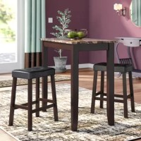 Whether you're looking to round out your entertainment ensemble, or pop a dining area into a cramped corner, a pub table and stools like this one is a great option for a touch of the handy surface area. Sized to seat two, this set includes a table and two stools. The table is crafted from solid wood, with a faux marble style finish on the surface. The stools feature wood bases with leather upholstered backless seats, so they can pull up directly beneath the table.