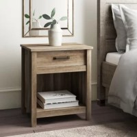 Bring  Mission style to your bedroom with this rustic one drawer nightstand. Crafted of manufactured wood in a wood grain finish, this nightstand strikes a rectangular silhouette featuring thick framing, oil rubbed bronze hardware, and straight square legs. Set on safety stop metal glides, one drawer offers out-of-sight storage for smaller accessories, while a cubby shelf provides plenty of space for other bedside essentials. Rounding out the design, the flat top surface provides a perfect...