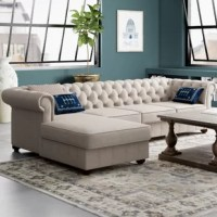 Whether you're curling up with the latest bestseller or sitting down for family movie night, this sectional offers a place to relax for every occasion. Measuring 29'' H x 112'' W x 66'' D, its L-shaped frame is crafted from rubber wood and wrapped in a polyester blend. Rolled arms, a button-tufted back, and bun feet solidify this piece's timeless appeal, making it a perfect pick for both modern and traditional ensembles alike.