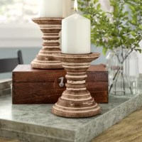 There's nothing quite like the romantic glow of candlelight to create the perfect ambiance for any occasion. Set a rustic, yet the refined foundation for your favorite pillar candle with this two-piece set of farmhouse-chic candlesticks! Crafted of wood, each candlestick features a heavily-distressed finish, while its lipped candle holder includes a removable spike to keep wax candles in place. Each candlestick accommodates one 4
