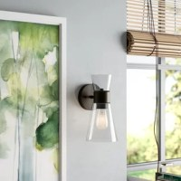Defined by its asymmetrical hourglass silhouette, this one-light armed sconce brings a splash of contemporary style to any space in your home. Crafted of metal, this fixture features a round backplate and a slender arm in a versatile bronze finish that pairs perfectly with most color palettes. Two tapered glass shades facing in opposite directions complete the look with a sleek touch, letting light from compatible 60 W medium-base bulbs (not included) pass both upwards and downwards.