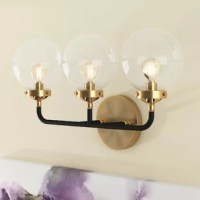 Taking cues from mid-century modern design, this three-light armed sconce features a trio of clear glass globe shades perched atop slender arms for a minimalist look. Three 25 W incandescent candelabra-base Edison bulbs (included) disperse ambient light throughout your space, while the fixture's two-tone brass gold and black finish create a striking contrast. Crafted of iron, this design is rated for damp indoor locations and can be safely installed in your bathroom.