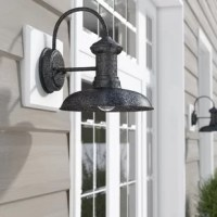 Bring some enhancing illumination to the exterior of your home with this 1-light wall sconce. A classic barn silhouette, this sconce offers simple, antique-inspired style. Made of metal, this hardwired luminary works well in dry, damp, or wet environments, so you can feel comfortable knowing it can be safely installed on your homes exterior walls. Accommodated beneath the round shade is one incandescent bulb of up to a maximum 75 W (bulb included).
