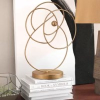 Looking for just the thing to round out your display or create and grab glances on a shelf? Sometimes all it takes is a decorative sculpture to lend a room a fresh look. Take this piece, for example: inspired by the orbits of celestial objects, this statuette features a single ball within connecting and overlapping rings. Crafted from metal with a gold leaf finish, this piece is perfect for a gleaming touch wherever it rests.