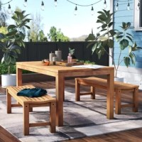 Enjoy alfresco meals on the patio or porch with this three-piece dining set. Crafted of solid teak wood in a light, natural stain, the dining table strikes a clean-lined rectangular silhouette with four chunky square legs. The tabletop features plank panel construction, while an umbrella hole lets you add your preferred parasol (not included) for meals in the shade. A pair of matching stools round out the set, each featuring contoured seats for added comfort and support. The table comfortably...