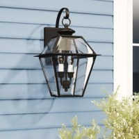 A traditional silhouette gets a contemporary refresh with this two-light outdoor wall lantern. Rated for use in wet locations, this metal fixture features a rectangular backplate, a curling arm, and a tapered body in a versatile bronze finish for understated appeal. Clear beveled glass panels make up the shade for a sleek touch, letting light from compatible candelabra-base bulbs (not included) pass through in an ambient direction. The manufacturer backs this product with a one-year warranty.