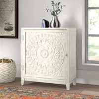 Form and function combine to create this must-have cabinet, perfect for adding a little extra space to stage decorative accents in any room of your home. Crafted from manufactured wood, its square silhouette features a distressed white finish, while the single door shows off a medallion in the style of a bas-relief. Inside, a shelf offers plenty of room to store serveware, napkins, or anything else you want out of sight but close at hand.