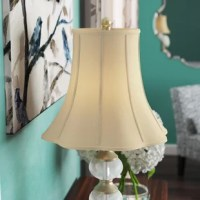 This lamp shade mimics the shape of a petunia flower and is just as beautiful. The soft scalloped edge at the bottom creates contrast and interest with your lamp base. Made of tailored silk-type shantung fabric with an off-white softback lining (black shades have gold softback lining) to create a warm, soft glow. A metal spider fitter in a brass finish helps accommodate light bulbs up to 150 W. The 14