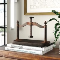 Add a distinctive accent to your bookshelf or console display with this decorative sculpture. Crafted from metal, it is designed to look like a vintage book press, and is finished in a hand-painted, rusted bronze finish for a distressed look. Though the press does crank up and down, it is not functional. Measuring 19.5'' H x 17.5'' W x 8.5'' D overall, it provides a sizable accent in homes with aesthetics ranging from modern farmhouse to vintage-inspired.