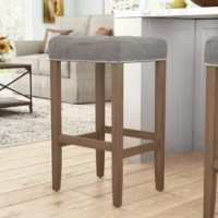 Bring charming farmhouse style to your pub table or kitchen counter with this bar stool. Enveloped in cotton and polyester-blend upholstery, this stool features a box seat accented by button tufting and gleaming nailhead trim, while cushioned padding provides comfort and support. Rounding out the design, the solid wood base includes four tapered legs and a built-in footrest. Measuring 30.25'' H x 17.75'' W x 15'' D overall, this stool has a 250 lbs. weight capacity.