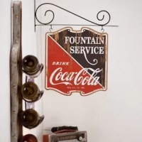 Finish off the look in your man cave, garage, home bar or game room with this Coca-Cola Double Sided Sign Wall Décor. Made from weathered and distressed wood as if straight out of a soda shop from the 1950's or 60's, this catchy piece of wall decor is a blast from the past. The distressed painted effect gives this sign a truly retro look and appeal. Whether you're looking to decorate your professional bar or pub or add some flair to your home bar, this dynamic signage will certainly draw...