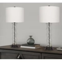 This unique glass table lamp set has just the right amount of sleek modern style and eye-catching flair. Each lamp's oil-rubbed bronze base supports a textured clear glass bamboo-inspired body embedded with gold sand and is crowned by a hardback drum shade wrapped in a crisp off-white linen.