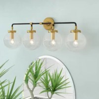 Designed to live in damp areas, like bathrooms with steamy showers, this vanity light is safe to shine over your sink. Crafted from metal, its frame features a circular backplate and a tubular bar finished in complementing matte black and brass. Measuring 11.5'' H x 31.5'' W, it includes four lights highlighted by glass globe shades, which can be installed facing either up or down. Assembly and installation are required for this hardwired luminary.