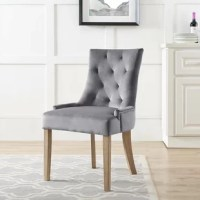 Update your dining room décor with this Lenoir Velvet Upholstered Dining Chair. Designed with a charming modern farmhouse aesthetic, this collection features elegant tufting, exquisite nailhead trim, padded seat and back with soft, stain-resistant velvet upholstery, and a décorative metal ring on the chair back for a delightful finishing touch. Supported by solid natural wood legs with flared back legs and non-marking foot caps, this is a distinctive dining chair perfect for the modern home.