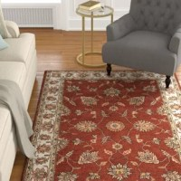 Like a piece of art, the central floral design on the rust-colored background of this Oriental-styled rug is framed by a contrasting parchment-hued border. Hand-tufted from soft 100% wool.
