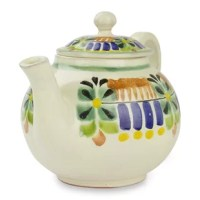 Painted by hand with colorful glazes, festive motifs envelop a teapot. This artisan works in the style of Mexico's colonial Majolica ceramics to create the design.