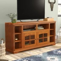 A must-have for living areas and entertainment spaces, this TV stand sets the stage for the big game, a movie marathon, or that season finale everyone's been talking about. This solid oak wood stand features two media storage areas enclosed with wood and glass doors, which open to reveal a fixed shelf. Its back panel features necessary ventilation and convenient cord cutouts, while an opening for your sound bar and media devices is easy for your remote to reach.