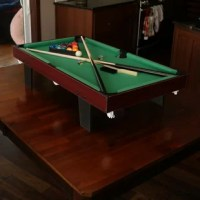 A Birdsong 3' Pool Table that offers the ultimate in table games so introduce billiards to friends and family with this fun, economical tabletop pool table. This pool table is made with durable MDF and PVC laminate and features a green felt surface. Plus, the compact size is big enough for a good game of pool but small enough so you can easily store it. The table comes complete with green felt, 2 cues, billiard balls, chalk, and a racking triangle. With this great kit, you can easily turn your...