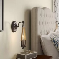 Searching for something special to spruce up the master suite? Switch out your nightstand lamp for this sconce on the wall above! Not only does it lende da a fashion-forward feel to your ensemble, but it also frees up space for displaying accents and keeping nighttime essentials on hand. Offering industrial appeal, this fixture features a teardrop-shaped stainless steel frame with rope elements and exposed candelabra-inspired light for an even gleam.