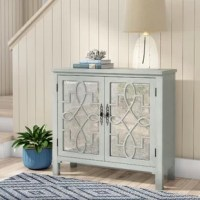 The Galvin 2 Door Accent Cabinet is transitionally styled and features 2 doors with antique mirrored glass set behind intricate open scroll fretwork, 1 fixed interior shelf, tapered legs, and a gray finish.