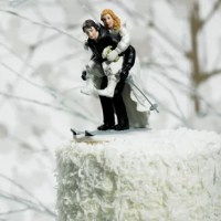 This Winter Skiing Cake Topper the gallant groom gives his new wife a piggyback as they ski the slopes of the wedding cake! For a winter wedding or ski enthusiast, this cozy couple is perfect for the top of your cake. Hand-painted porcelain.