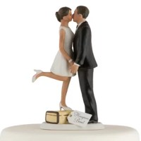 This couple A Kiss and We're off Cake Topper, shows all the excitement of a bride and groom about to start on their first journey together as husband and wife. While perched on a suitcase the Bride steals a precious moment to kiss her groom.