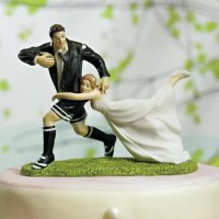 This Tackle Bride and Groom Cake Topper fun couple are sure to make your guests giggle as the bride tackles her rugby player groom! A unique and personal cake topper option for rugby fans. Hand-painted porcelain.