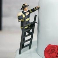 This Fireman Groom Cake Topper, a groom is all decked out in his firefighting gear and climbing a ladder to get to his bride. He is held in place by two pegs on the ladder so simply lean him up against one of the bottom tiers of your wedding cake and he is all set to rescue his bride.