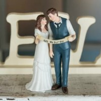 The Indie Style Couple Cake Topper of this product is cool and classic. The retro-inspired attire and hairstyles are practically perfect for vintage themed weddings. This couple stares lovingly into each other's eyes while confidently holding up a banner declaring