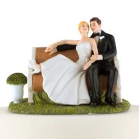 A serene celebration, this Sitting On A Bench Cake Topper couple is snuggling on a picturesque park bench. As the bride puts her feet up to cuddle against her groom, he places his hand on hers as they celebrate becoming man and wife.