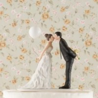 This Leaning in for a Kiss Cake Topper couple is sweetly leaning forward for a kiss as husband and wife! Wearing a beautiful bowed dress and clasping a balloon, this beautiful bride is leaning towards her one true love as he holds onto her bouquet.