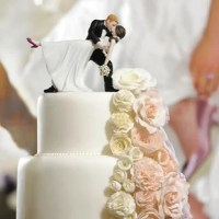 This Dancing Bride and Groom Cake Topper product is wrapped in a romantic embrace of dance. The bride's pretty ponytail, simple dress, and rhinestone shoes give this product a lovely modernized twist on a classic pose. Personalize the look by selecting a colored shoe for the bride. Hand-painted porcelain.