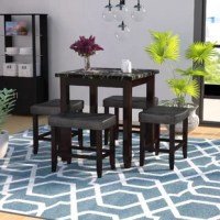 Looking to elevate your in-home dining experience? This five-piece counter-height set should do the trick. A stylish blend of traditional and today, this set transitions well with any evolving look. The dining table stands 36'' tall and measures 32'' square, with warm, espresso-finished legs and a faux marble tabletop for a hint of organic influence, while four matching saddle-seat stools – each padded with foam and wrapped in faux leather upholstery – round out the ensemble. To save space...