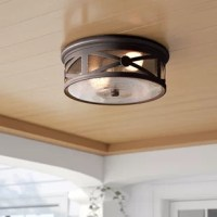 Cast a warm and welcoming glow over the entrance to your home with this two-light outdoor flush mount. Rated for damp locations like a covered porch or patio, this aluminum fixture features a cylindrical silhouette with classic cross overlay along all sides in a versatile solid finish. Clear seeded glass makes up the shade for a hint of vintage flair, while a pair of 60 W medium-base incandescent bulbs (not included) sits within to offer a boost of brightness.