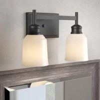 Bathroom remodels come in many forms, but across all of them, one thing remains the same: Lighting matters. Layers of lighting turn tiny washrooms into statement-makers and large-scale bathrooms into spa sanctuaries. Take this vanity light for example: Crafted from metal, its frame features a clean-lined silhouette and boasts a neutral black finish. Two bell shades made from glass sport a white finish and each accommodate one 100 W E26 lightbulb (not included).